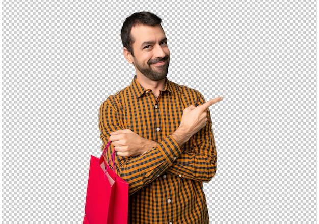 Uomo con borse della spesa che punta al lato per presentare un prodotto Psd Premium