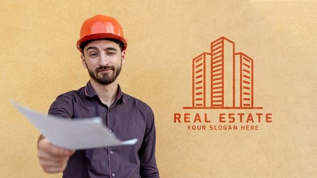 Uomo con cappello duro in possesso di un documento sfocato Psd Gratuite