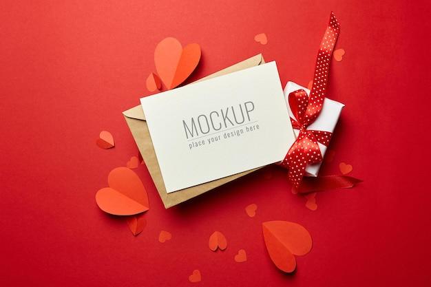 Valentijnsdag kaartmodel met envelop, geschenkdoos en rode papieren harten Premium Psd