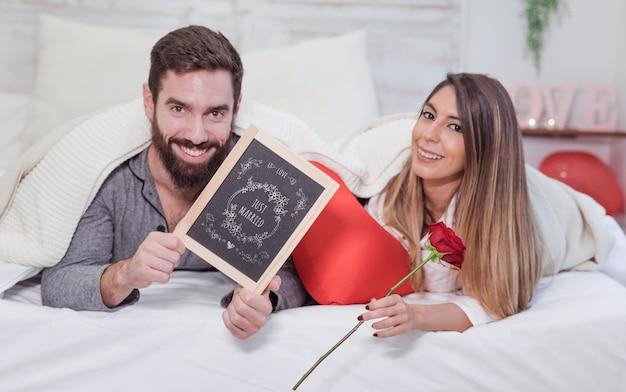 Valentine-mockup met paar in bed die lei tonen Gratis Psd