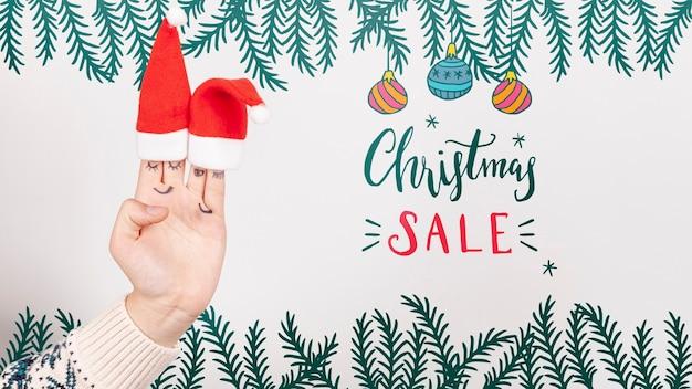 Venta de navidad con gorro de papá noel en una mano PSD gratuito