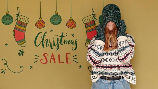 Venta de navidad y mujer cubriéndose la cara con un sombrero PSD gratuito