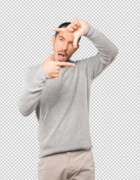 Verbaasde jonge man die een gebaar maakt van het nemen van een foto met de handen Premium Psd