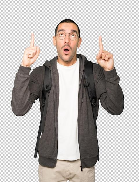 Verbaasde student die met zijn vinger omhoog wijst Premium Psd