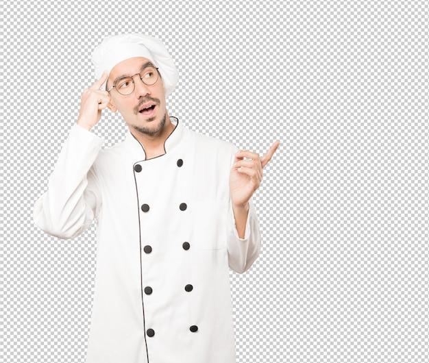 Verraste jonge chef-kok die een gebaar van concentratie doet Premium Psd
