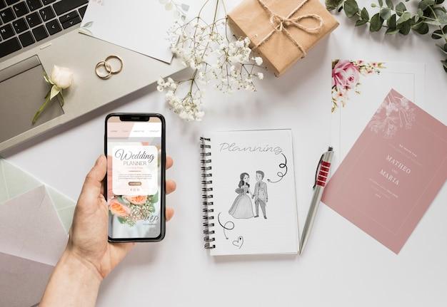 Vet leg van de hand met smartphone en bruiloft essentials Gratis Psd