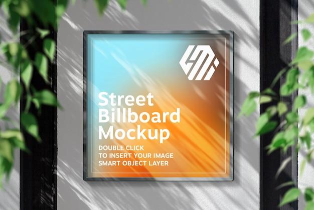 Vierkant reclamebord opknoping op zonovergoten muur mockup Premium Psd