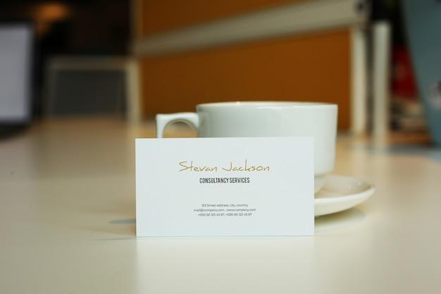 Visitekaartje mockup psd met koffie of cappuccino of theekop Premium Psd