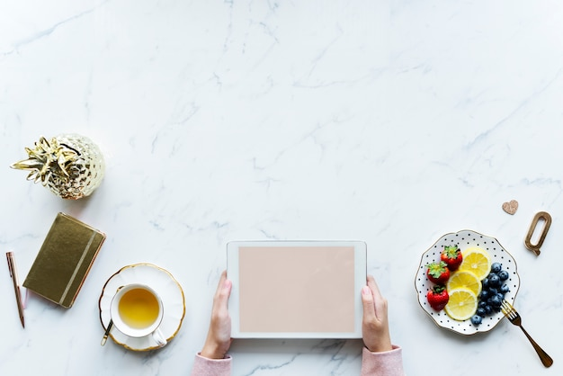 Vista aerea della donna che utilizza una compressa digitale su una tavola di marmo con lo spazio di progettazione Psd Gratuite