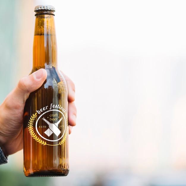 Vista frontal botella de cerveza en poder de la persona PSD gratuito