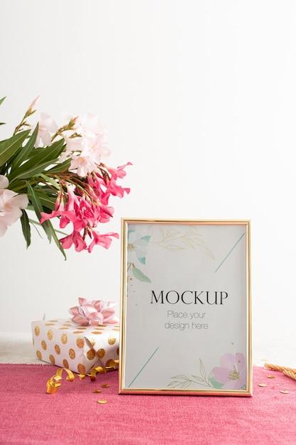 Vista frontal del elegante marco de cumpleaños con flores y presente PSD gratuito