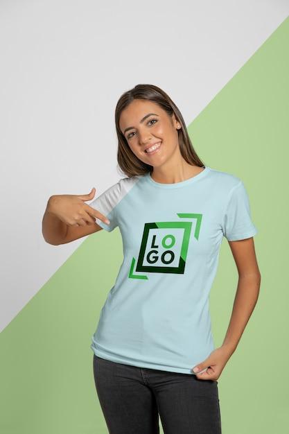 Vista frontal de la mujer apuntando a la camiseta que lleva puesta PSD gratuito