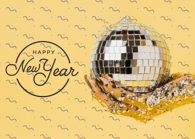 Vista frontal mujer sosteniendo bola de discoteca con letras de año nuevo PSD gratuito