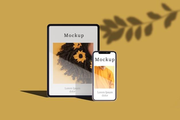 Vista frontale della compressa e dello smartphone con l'ombra delle foglie Psd Gratuite