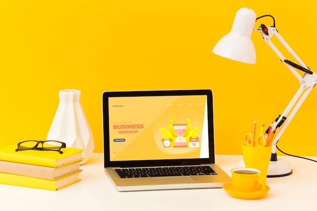 Vista frontale della scrivania con lampada e laptop Psd Gratuite
