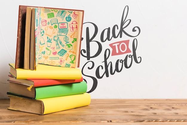 Vista frontale di nuovo a scuola con una pila di libri Psd Gratuite