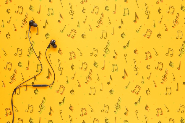 Vista superior de auriculares sobre fondo amarillo con espacio de copia PSD gratuito