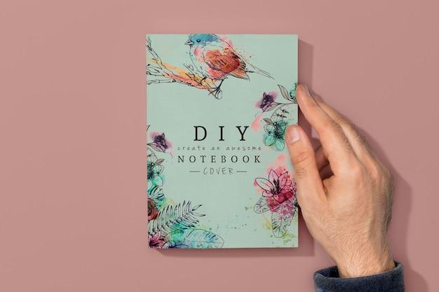 Vista superior de la mano en la maqueta del libro PSD gratuito