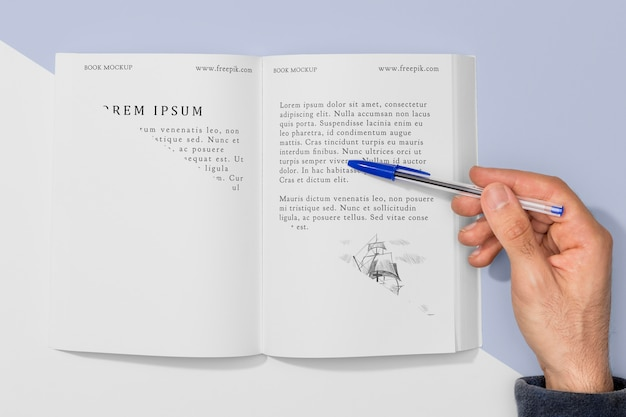 Vista superior mano sosteniendo la pluma sobre la maqueta de libro abierto PSD gratuito