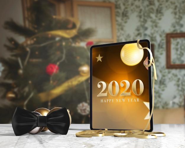 Vlinderdas naast tablet met bericht voor nieuw ja Gratis Psd