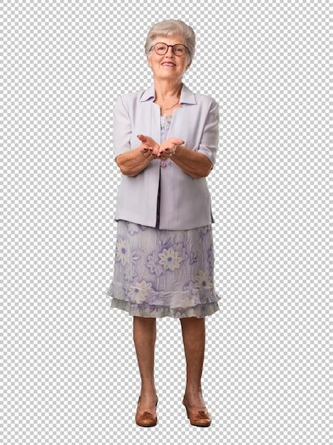Volledige lichaam hogere vrouw die iets met handen houdt, die een product toont, glimlachend en vrolijk, die een denkbeeldig voorwerp aanbiedt Premium Psd