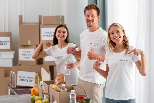 Voluntarios sonrientes señalando sus camisetas mientras preparan la comida para la donación PSD Premium