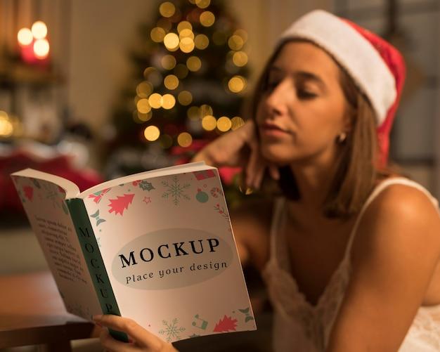 Volwassen vrouw die een kerstmisboek met model leest Gratis Psd