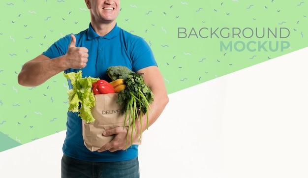 Vooraanzicht bezorger met een doos met verschillende groenten mock-up Gratis Psd