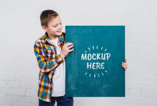 Vooraanzicht jong kind met mock-up teken Gratis Psd