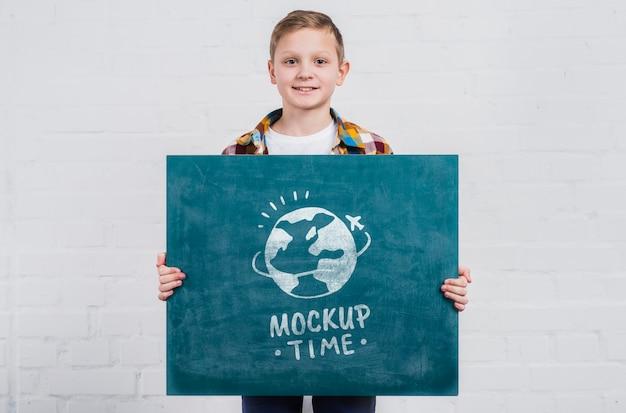 Vooraanzicht jonge jongen met mock-up teken Gratis Psd