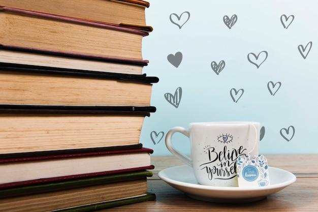 Vooraanzicht kopje koffie met label en stapel boeken Gratis Psd