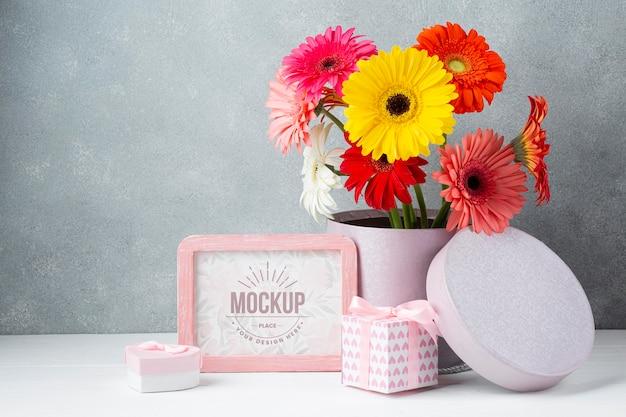 Vooraanzicht van daisy pot met geschenken en frame Gratis Psd