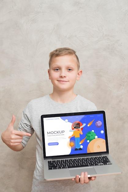 Vooraanzicht van kind houden en wijzen op laptop Premium Psd
