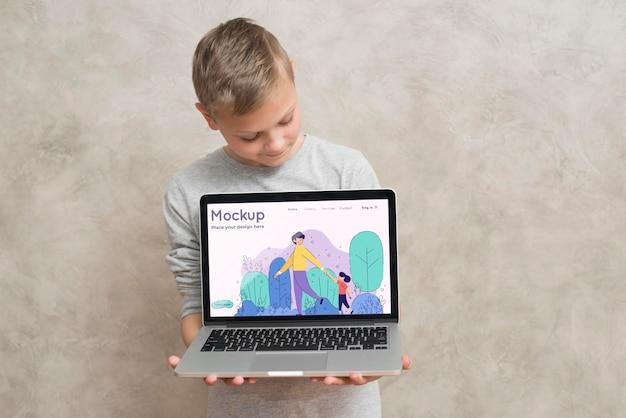 Vooraanzicht van laptop van de jongensholding Gratis Psd
