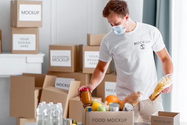 Vooraanzicht van mannelijke vrijwilliger die met medisch masker voedselschenkingsdoos voorbereiden Gratis Psd
