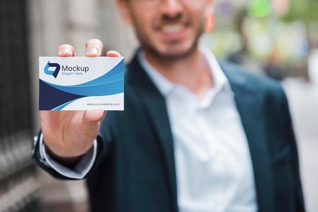 Vooraanzicht van onscherpe de holdingsvisitekaartje van de smileyzakenman Gratis Psd
