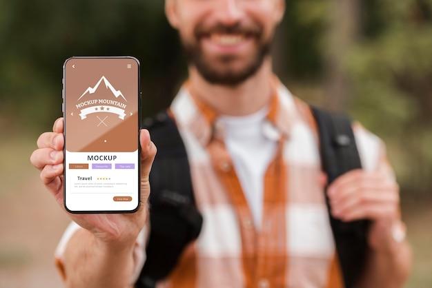 Vooraanzicht van smiley man met smartphone tijdens het kamperen Gratis Psd