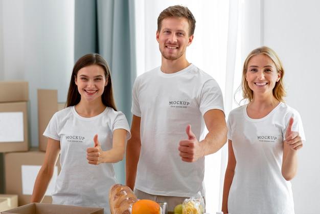Vooraanzicht van smileyvrijwilligers die duimen opgeven Premium Psd