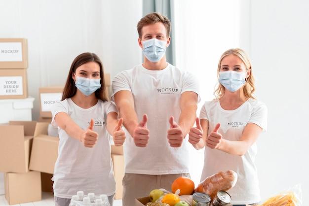 Vooraanzicht van vrijwilligers met medische maskers die duimen opgeven Gratis Psd