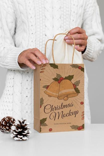 Vooraanzicht van vrouw met kerst papieren zak met dennenappel Gratis Psd