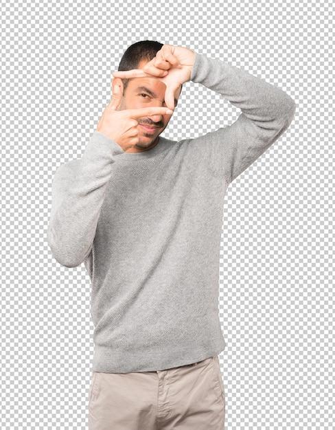 Vriendelijke jonge man die een gebaar maakt van het nemen van een foto met de handen Premium Psd