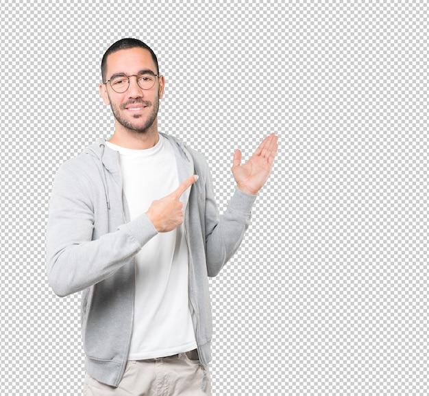 Vriendelijke jonge man die een welkom gebaar maakt Premium Psd