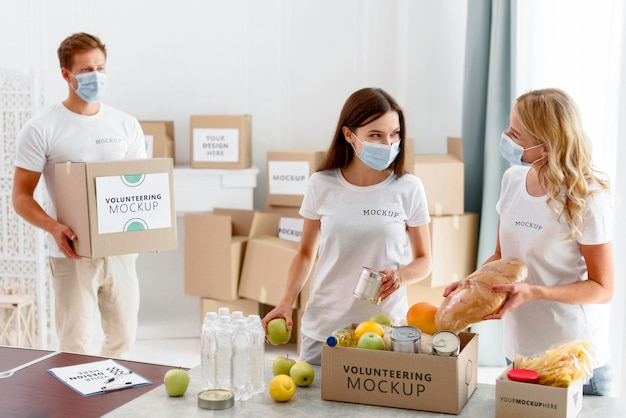 Vrijwilligers met medische maskers maken provisieboxen klaar voor donatie Gratis Psd