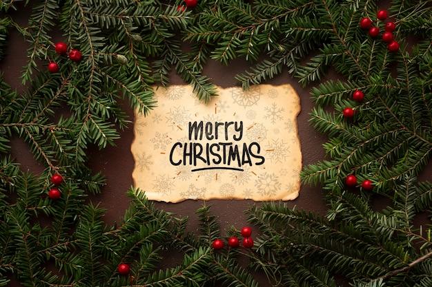 Vrolijk kerstfeest op een vintage papier en kerst pijnboombladeren Gratis Psd