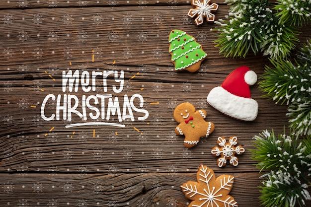 Vrolijke kerstmis met peperkoek en kerstmispijnboombladeren Gratis Psd