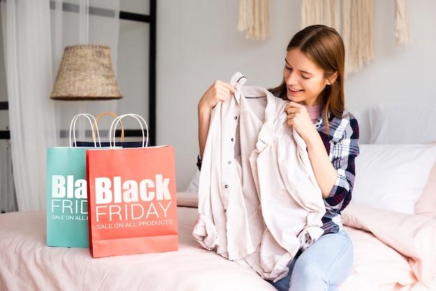 Vrouw die een doek van een zwarte vrijdagzak neemt Gratis Psd