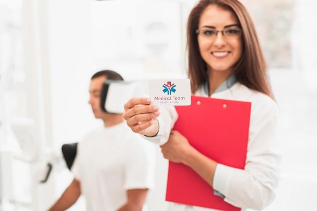 Vrouw die een klembord en een model klinische kaart houdt Gratis Psd