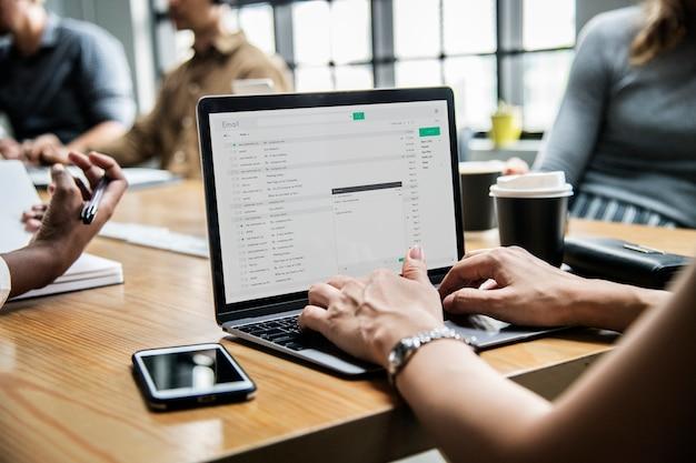 Vrouw die haar e-mail in een vergadering controleert Gratis Psd