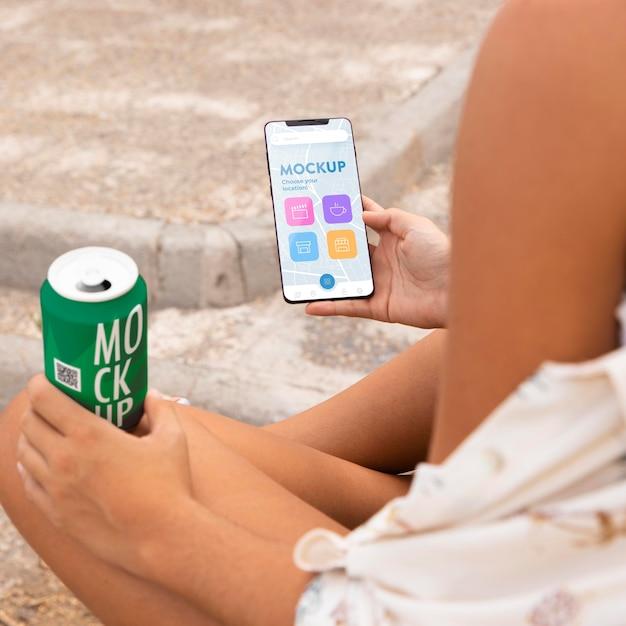 Vrouw die haar smartphone controleert terwijl het drinken van frisdrank Gratis Psd