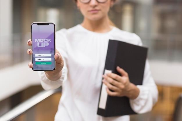 Vrouw die haar telefoonscherm toont Gratis Psd